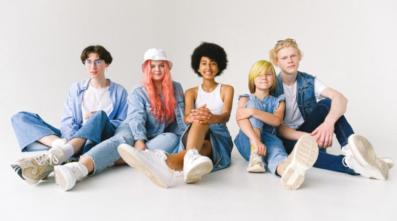 Smiling multiracial teenagers and child in casual apparel in studio by Anna Shvets